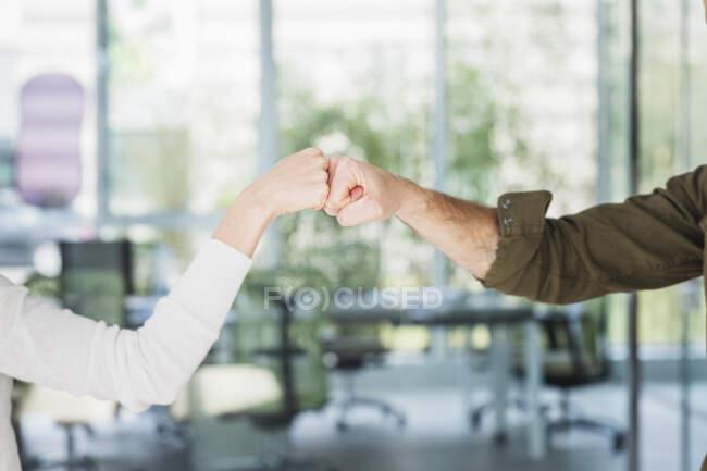 Männliche und weibliche Kollegen grüßen mit Faustschlägen im Amt — Stockfoto