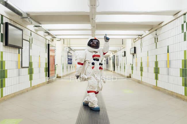 Astronauta apuntando mientras está de pie en el metro - foto de stock