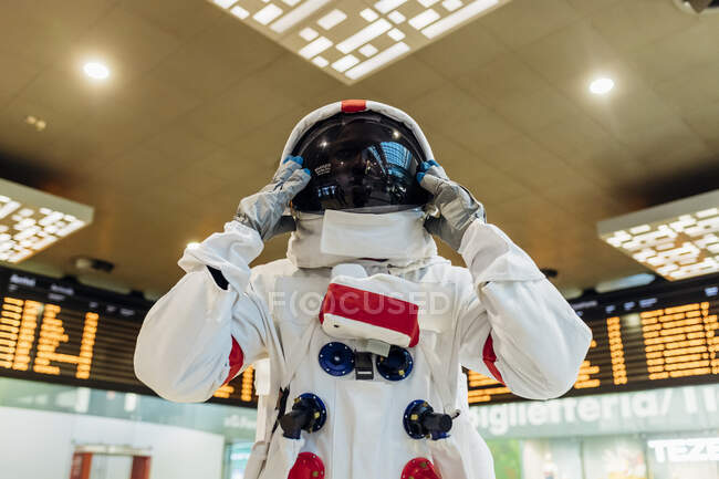 Male astronaut wearing space helmet while standing at arrival departure board - foto de stock