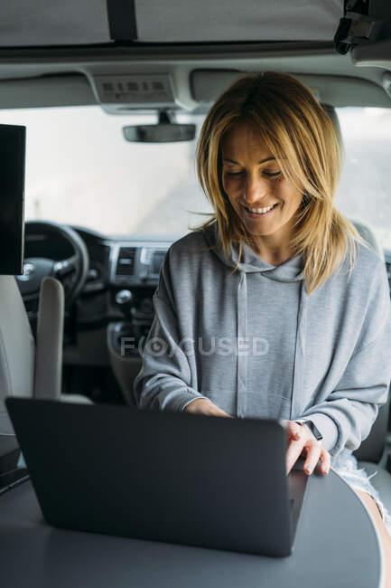 Profissional feminino usando laptop enquanto na van — Fotografia de Stock