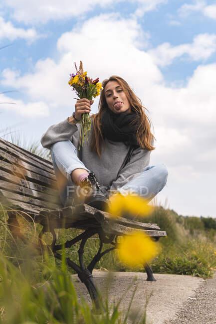 Giovane donna sporgente lingua mentre seduto con mazzo di fiori sulla panchina — Foto stock