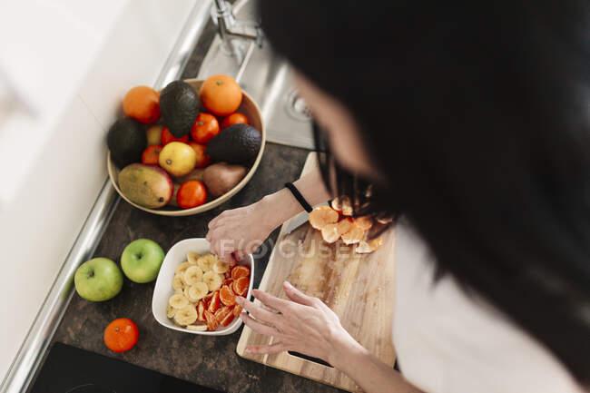 Mulher preparando tigela de frutas no balcão da cozinha em casa — Fotografia de Stock