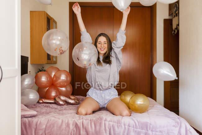 Mujer alegre jugando con globos mientras se arrodilla en la cama en casa - foto de stock
