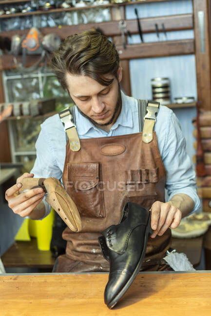 Empreendedor masculino segurando sapato maca enquanto olha para sapato na oficina — Fotografia de Stock