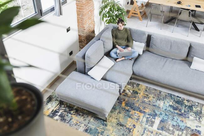 Молода жінка, сидячи вдома на дивані, користується ноутбуком. — стокове фото
