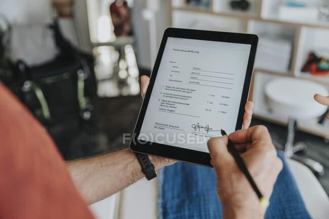 Paciente masculino firma digitalmente formulario en la práctica - foto de stock