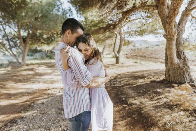 Улыбающаяся девушка обнимает парня на улице — стоковое фото