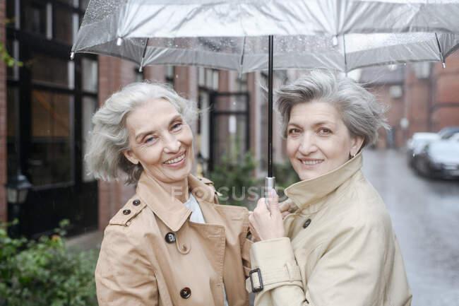 Усміхаючись, дівчата тримають парасольку під час дощового дня. — стокове фото