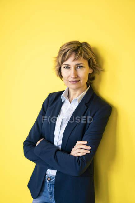 Fiduciosa donna d'affari appoggiata alla parete gialla — Foto stock