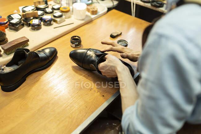 Macho artesão aplicando polonês no sapato na oficina — Fotografia de Stock