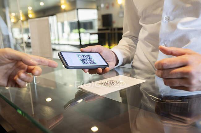 Hombre maduro mostrando el código QR en el teléfono móvil en la recepcionista escritorio del hotel - foto de stock