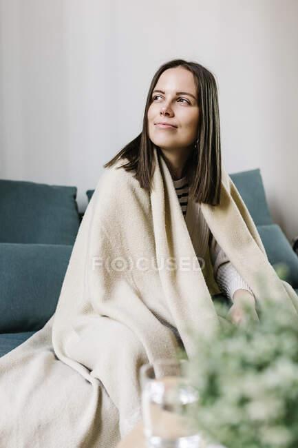 Mujer enferma envuelta en manta mirando hacia otro lado mientras está sentada en casa - foto de stock