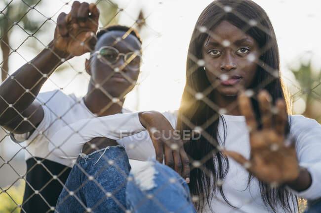 Novio y novia sosteniendo valla mientras está sentado al aire libre - foto de stock