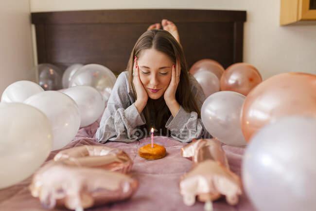 Mujer con la cabeza en las manos mirando a la vela en donut mientras está acostada en medio de globos - foto de stock