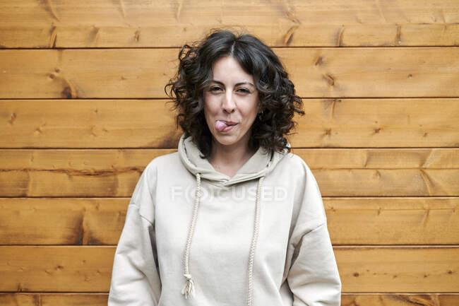 Donna felice sporgere la lingua mentre in piedi davanti al muro di legno — Foto stock