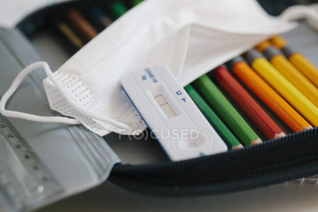 Kit de diagnóstico rápido con mascarilla protectora en estuche de lápiz en la escuela - foto de stock