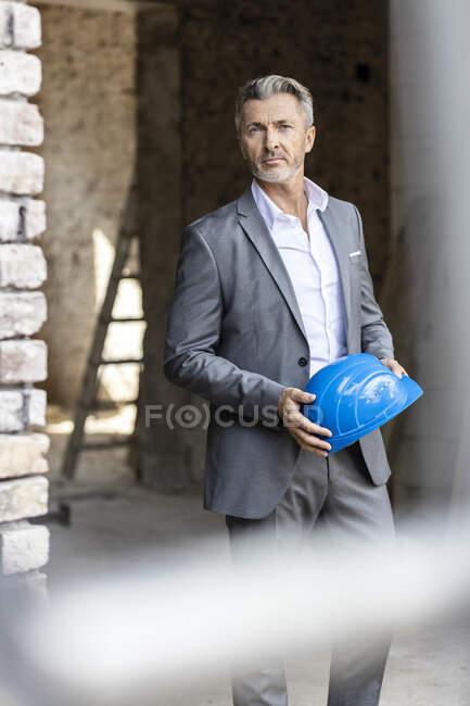 Arquiteto masculino segurando hardhat enquanto estava de pé no local de construção — Fotografia de Stock