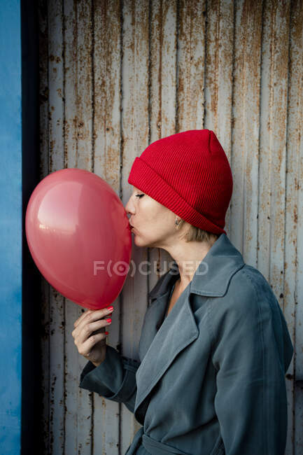 Mid adult woman kissing balloon while standing by corrugated shutter - foto de stock