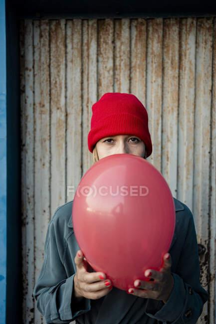 Взрослая женщина держит красный шарик перед гофрированным железом — стоковое фото