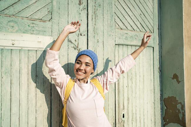 Mujer hermosa alegre con los brazos levantados mirando hacia otro lado delante de la puerta durante el día soleado - foto de stock