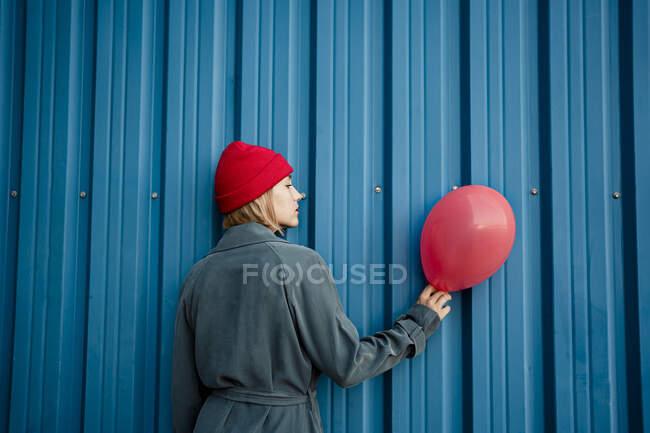 Mujer adulta sosteniendo globo rojo por obturador azul - foto de stock