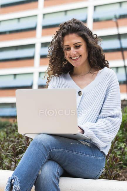 Mulher sorrindo usando laptop enquanto sentado na parede de retenção — Fotografia de Stock