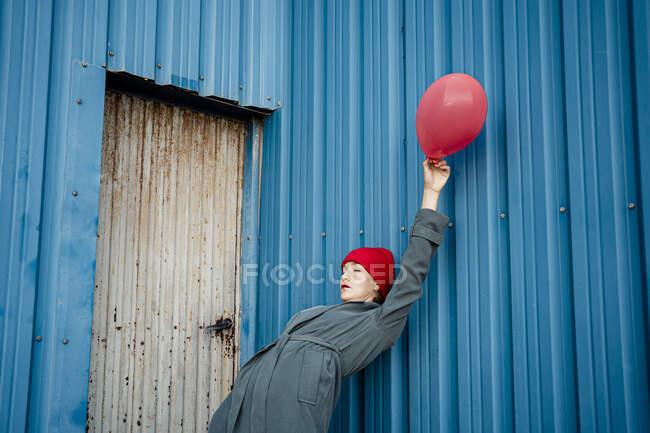 Mujer sosteniendo globo mientras se inclina hacia atrás en obturador azul - foto de stock