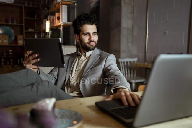 Заручний чоловічий підприємець з цифровим планшетом працює на ноутбуці в кафе. — стокове фото