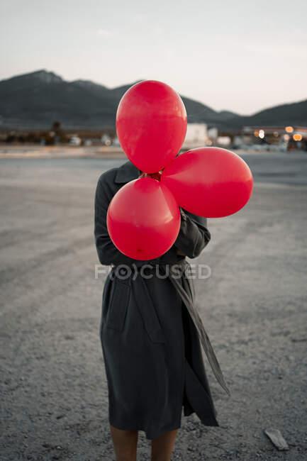 Взрослая женщина, покрывающая лицо красным шаром, стоя на дороге — стоковое фото