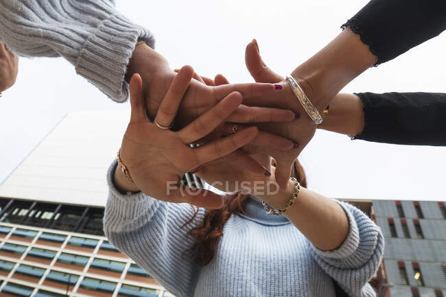 Young female friends stacking hands — Stock Photo