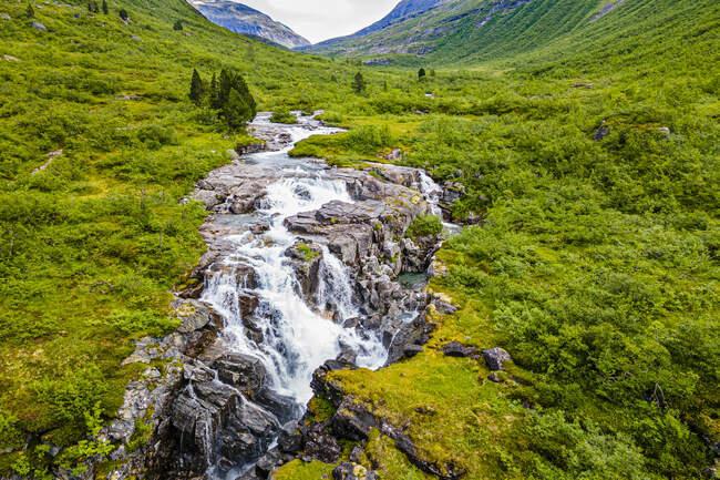 Cascada que fluye a través de rocas en el verde valle de montaña - foto de stock