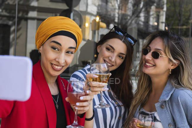 Jeune femme prenant selfie avec des amies tout en prenant des boissons — Photo de stock