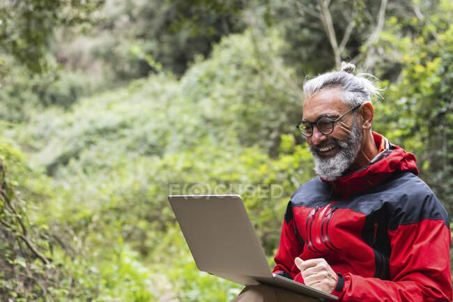 Усмішка старшого чоловіка, який користується ноутбуком, сидячи в лісі. — стокове фото