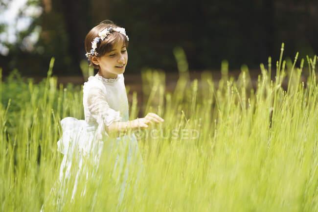 Дівчинка у білій сукні торкається трави в день її причастя. — стокове фото