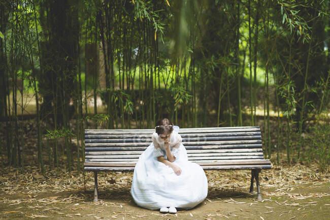 Дівчина з підборіддям у білій сукні сидить на лавці в парку. — стокове фото