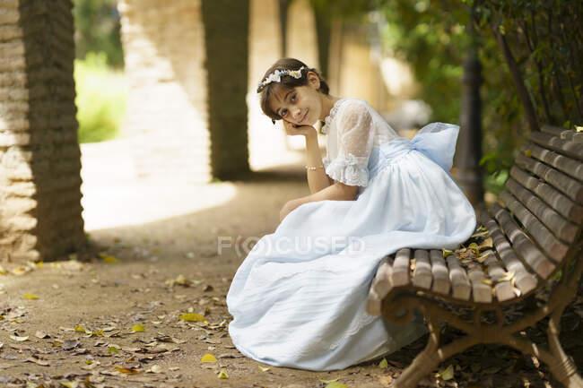 Мила дівчина у білій сукні з підборіддям у громадському парку. — стокове фото