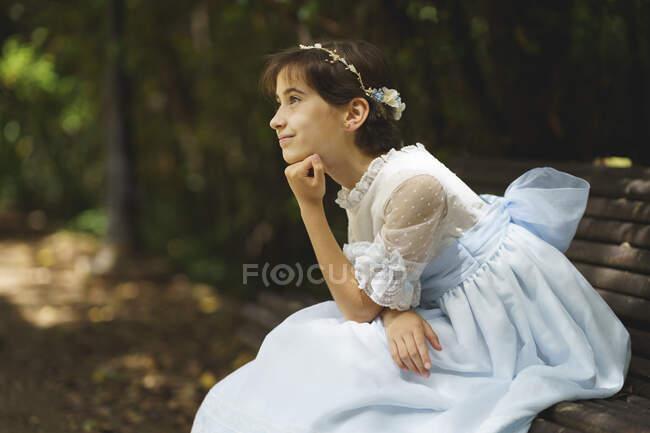 Дівчата в білому вбранні для спілкування мріють, сидячи на лавці в парку. — стокове фото