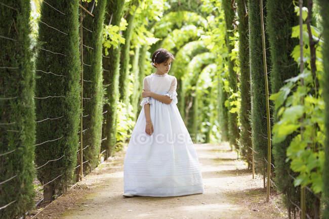 Дівчинка у білому причастя дивиться вниз, стоячи в саду. — стокове фото