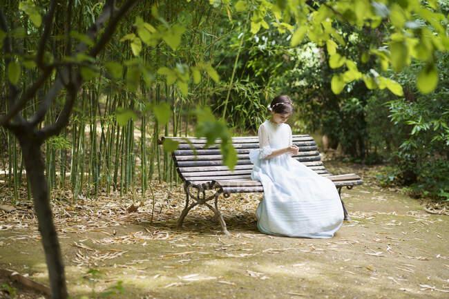 Дівчинка у білому вбранні для спілкування сидить на лавці в парку. — стокове фото