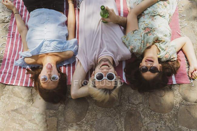 Uomo sorridente sdraiato tra amici femminili che sporgono la lingua mentre si rilassa sulla coperta — Foto stock