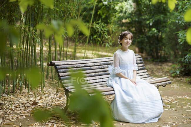 Усміхнена дівчинка сидить у білій сукні на лавці парку. — стокове фото