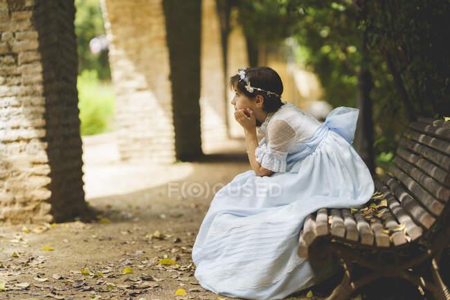Дівчинка з підборіддям роздумує, сидячи на лавці. — стокове фото