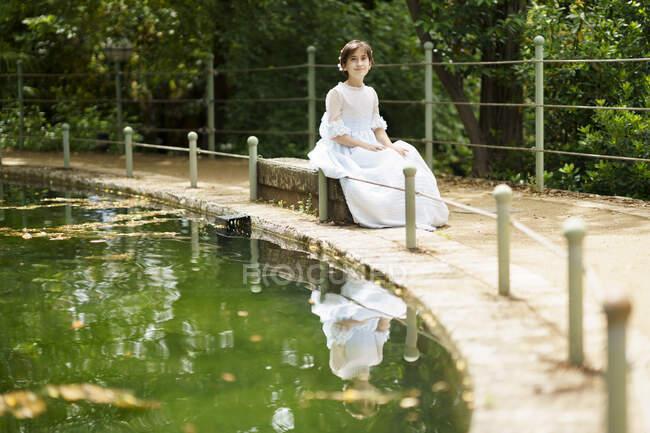 Дівчинка у білій сукні сидить на скелі біля ставка в саду. — стокове фото