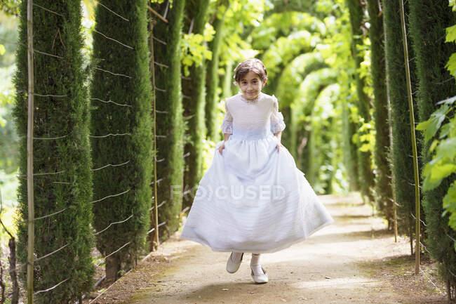 Мила дівчина у білому пристойному одязі біжить стежкою в зеленому саду. — стокове фото