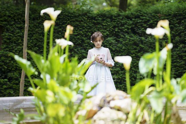 Дівчинка у білому вбранні для спілкування з камерою в парку. — стокове фото