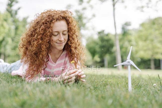 Улыбающаяся молодая женщина с вьющимися волосами, лежащая на траве в парке — стоковое фото