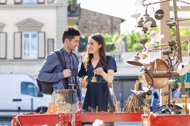 Улыбающаяся женщина держит колокольчик и кредитку, стоя рядом с мужчиной на уличном рынке — стоковое фото