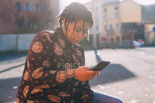 Jovem mulher usando telefone celular no dia ensolarado — Fotografia de Stock