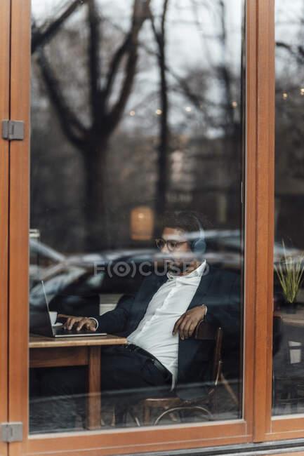 Бизнесмен использует ноутбук, слушая музыку в кафе через стекло — стоковое фото