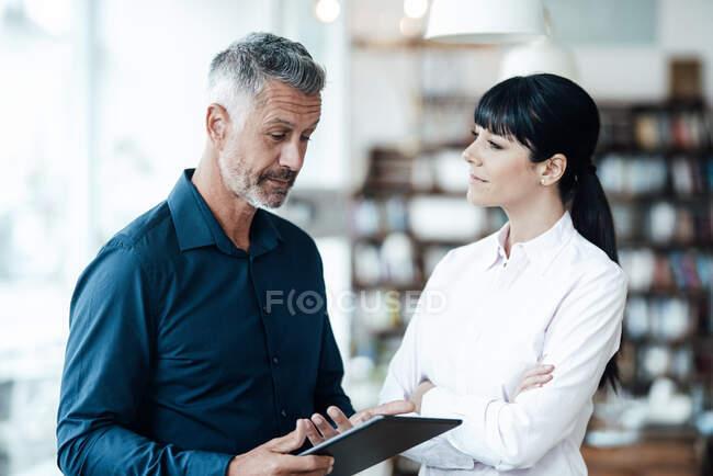 Женщина-предприниматель слушает коллегу, стоящую за цифровым столом в кофейне — стоковое фото
